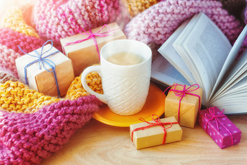 A сup of tea, wrapped gifts and an open book on the background of a knitted blanket.