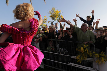 Artist throws flowers during the flower parade as part of the Carnival of Nice