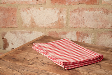 Empty wooden table with tablecloth over brick stone wall background.