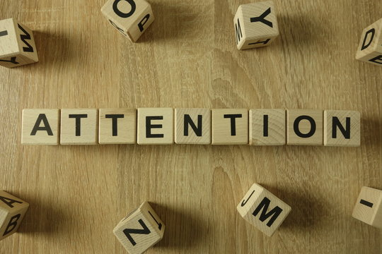 Attention word from wooden blocks on desk