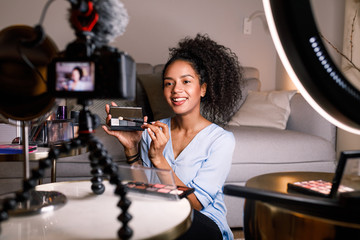 Smiling woman holding a makeup palette while recording her video for blog