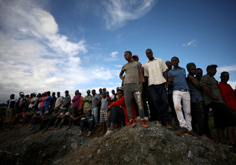Onlookers wait for news as retrieval efforts proceed for trapped artisanal gold miners near Kadoma