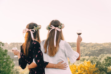 Two young girls hug during sunset in the field with wine glasses friendship concept copy space
