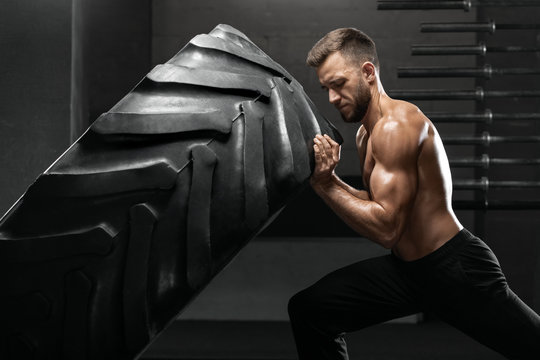Muscular man working out in gym flipping tire, strong male naked torso