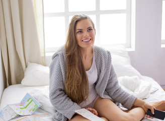 Happy young girl in bed using phone, tablet and maps to search for travel