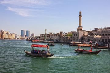 Dubai, UAE - Feb 15, 2019: Tourist boats abra on canal Dubai Creek and old town.