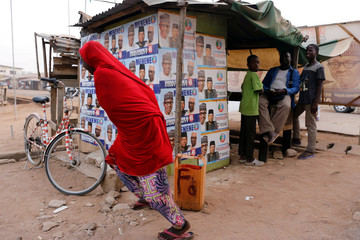 A girl runs past a shack covered in election posters, after the postponement of the presidential election in Yola, Adamawa State