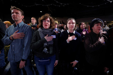 Audience members recite the U.S. pledge of allegiance before a campaign stop with Democratic 2020 U.S. presidential candidate Booker in Portsmouth
