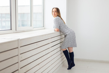 people, fashion and beauty concept - young woman in wool dress posing near window sill