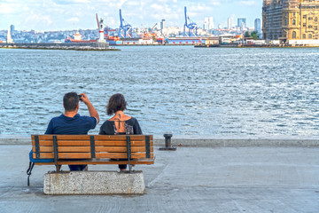 modern couple sitting at waterfront