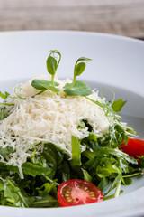 fresh tasty healthy rucola salad in white plate