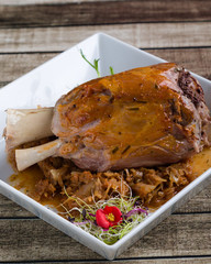 bavarian pork knuckle with cabbage on white plate