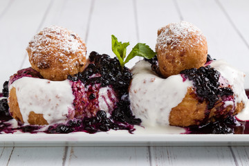 fresh delicious cottage cheese donuts with jam on white plate