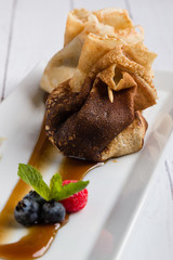 european pancakes, sweet crepe with topping on white long plate