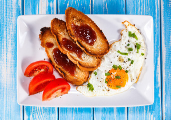 Breakfast - fried egg, toasts and vegetable salad