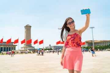 Wall Mural - Asian tourist woman taking selfie photo with phone in Beijing, China. Asia travel famous destination girl holding cellphone visiting Tiananmen Square, popular tourism attraction. Summer vacation.