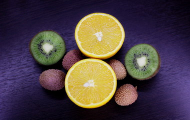 still life of citrus, juicy kiwi and orange in the cut and Litchi chinensis on a dark background