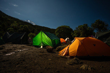 Lighted tents in front of Kilimanjaro, under the stars