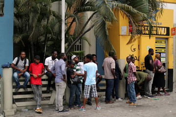 People line up outside a money transfer point at a neighborhood in Port-au-Prince