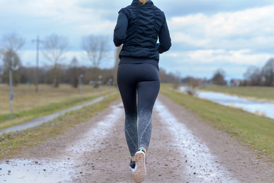 Fit healthy young woman jogging away from camera