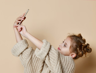 Pretty modern girl in huge sweater smiling and making selfie on smartphone