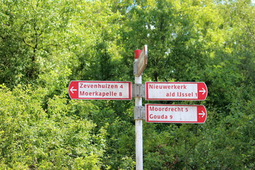 Red white direction signs for cyclist to several villages in Zuidplas, the NeteRLANDS
