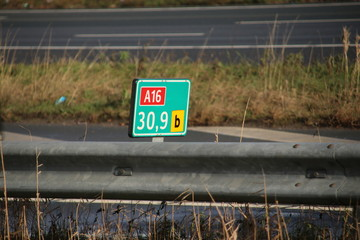 Green and white distance sign in kilometers at a shoulder along motorway A16 at Zwijndrecht in the Netherlands