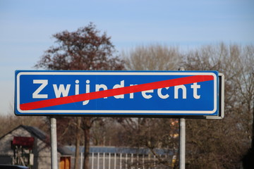 Red white sign with red line that indicates the end of the urban area of the city of Zwijndrecht in the Netherlands