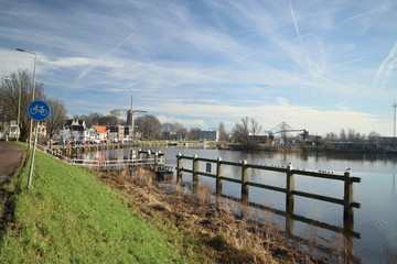 Oude Veerstal along the quay of river Hollandsche IJssel with windmill 't Slot in Gouda, the Netherlands