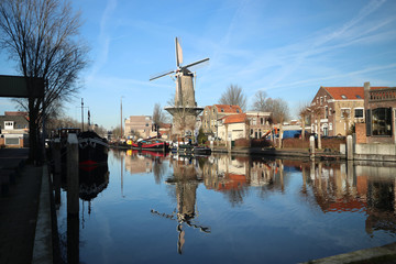 Windmill de Roode Leeuw with reflection in the Turfsingel in Gouda with sails on it