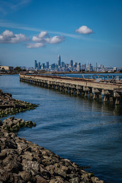 Very rocky shore zigzags next to a dock with bright blue water leading to the San Francisco skyline at the Alameda Ferry Terminal