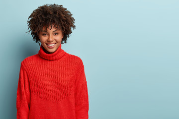Sincere feminine girl with dark skin, crisp hair, broad smile, has fun, enjoys evening in good company, wears red sweater with collar, models over blue background with free space on right side Fototapete