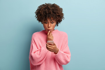 Candid shot of surprised black lady stares at screen of cell phone, amazed with discounts in web store, reacts emotionally on broadcast, connected to wireless internet, isolated on blue background