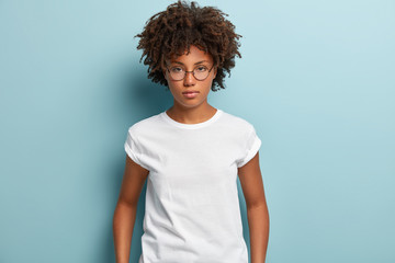 Studio shot of serious thoughtful feminine girl with dark skin, crisp hair, looks directly at camera, wears spectacles and t shirt, thinks over problematic situation, isolated over blue background