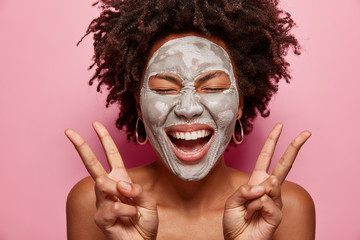 Joyful ethnic woman has white face rejuvenation mask, natural beauty, Afro hairstyle, makes peace sign with both hands, smiles broadly, isolated over pink background. Cosmetic treatments concept