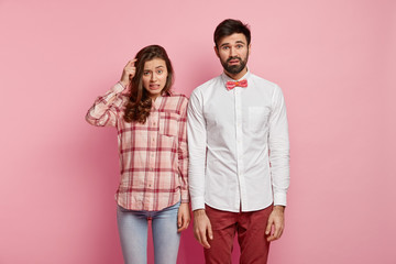 Bewildered woman scratches head, stands near boyfriend, have clueless expressions, try to find decision, wear stylish clothes, stand over rosy background. So, where is way out? Puzzlement concept