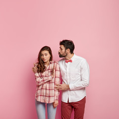 Photo of attractive woman shows refusal gesture, doesnt want to recieve kiss from boyfriend, who cuddles and keeps lips folded, wear fashionable clothes, isolated over pink background with copy space