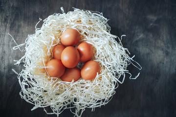 Wood wool eggs, dark wooden background. Top viewEggs on wood wool nest. Top view