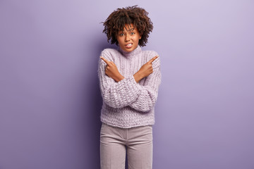 Dark skinned young woman with curly hairstyle, crosses hands over chest, points at sifferent sides, makes decision or choice, wears casual sweater and trousers, isolated over purple background