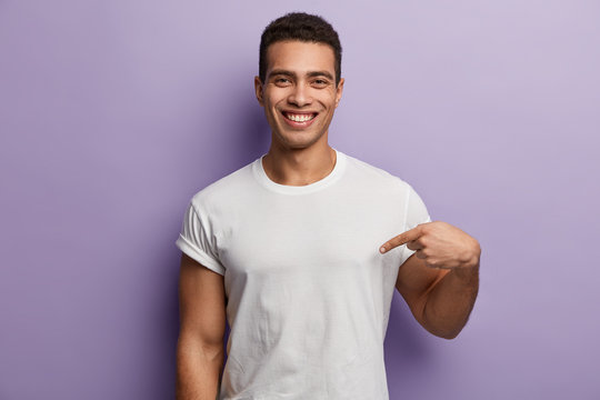 Look at my new t shirt. Indoor pleased Caucasian man with short haitcut, points at blank space of his clothes, smiles positively, isolated over purple background. Advertisement and clothing concept