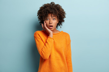 Indoor shot of stupefied frightened woman with dark skin, crisp hair, keeps hand on cheek, wears orange jumper, has surprised gaze at camera, models over blue background. Facial expressions concept