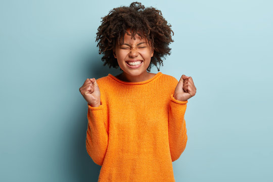 Oh yes finally I gained it! Overjoyed pleased dark skinned young woman raises clenched fists, shows white teeth, wears orange sweater, models over blue background, celebrates excellent news.