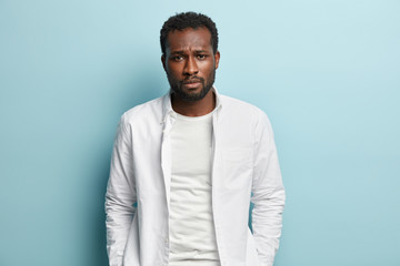 Image of sad sorrowful black man with thick bristle, wears white shirt, feels troublesome, looks at camera with miserable expression, isolated over blue background. People, melancholy, problem concept