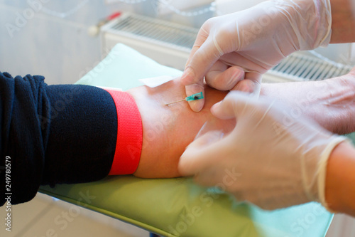 Close up of doctor hands taking blood from male vein into