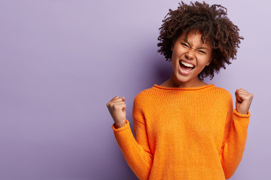 Life is wonderful! Joyful dark skinned lady keeps fists clenched, tilts head and exclaims in triumph, celebrates success, isolated over purple background with blank space for your advertisement