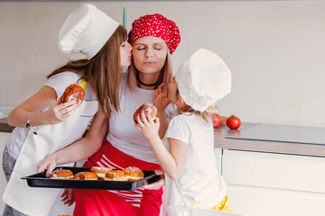 young girls and mother in chef clothes with baked donuts