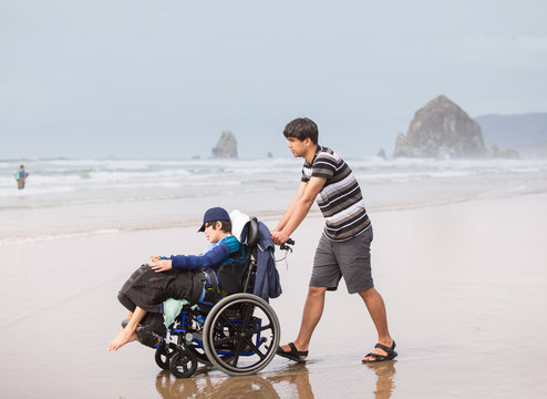 Young man pushing disabled brother in wheelchair on beach