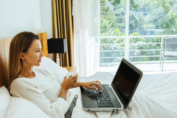 Woman using laptop in the bed