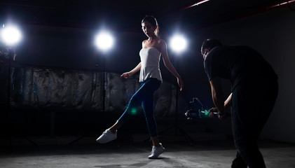 Asian slim Fitness woman exercise warm up ballet dance stretch body arm legs jump in white shirt jean pants Smoke Dark background environment, studio lighting rim back light low exposure copy space