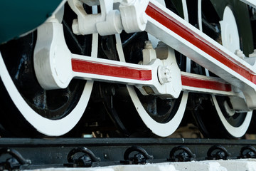 Closeup wheel of train. Green red and white train. Antique vintage train locomotive. Old steam engine locomotive. Black locomotive. Old transportation vehicle.